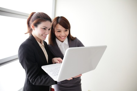Business women look and smile conversation with computer in Office, asian photo