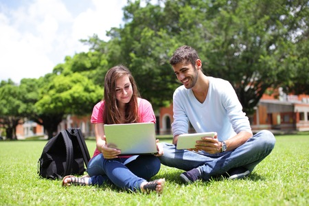 Happy College students using laptop and tablet pc on campus lawn, caucasian photo