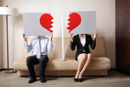 broken home: Divorce - Sad young couple holding billboard sign with break love heart, concept for divorce Stock Photo