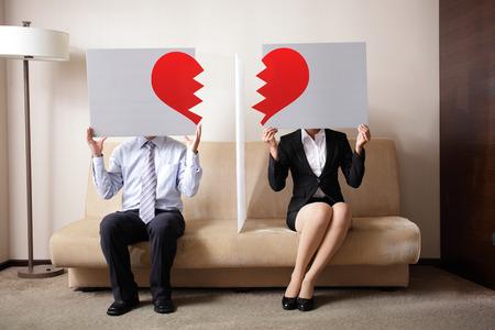Echtscheiding - Sad jonge paar bedrijf billboard teken met break liefde hart, concept voor echtscheiding Stockfoto