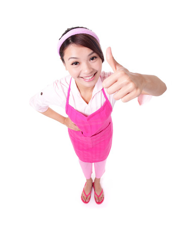Happy young woman housewife mother wearing kitchen apron and showing thumbs up, asian photo