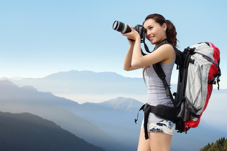 backpackers: Young woman with backpack taking a photo on the top of mountains, asian Stock Photo