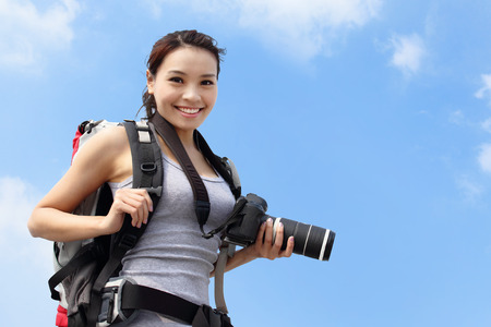 travellers: Young woman mountain hiker holding camera with sky background, asian