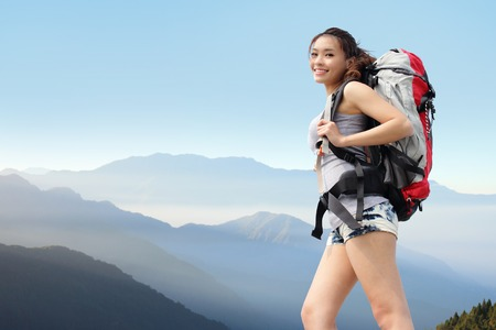 happy woman mountain hiker with backpack and smile to you on the top of mountains. asian photo