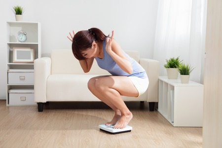 woman on scale: Upset woman on weigh scale at home, asian