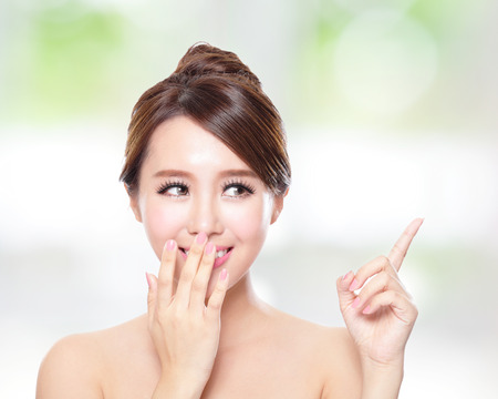 finger on lips: attractive woman with health skin and teeth, she is happy talk to you with nature green background, asian