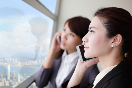 Business woman speaking phone and looking through window with city background, asia, hong kong, asian photo