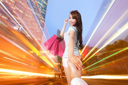 Happy Shopping in hong kong - beautiful young woman holding colored shopping bags at night, asian photo