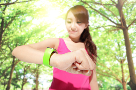 Health sport woman wearing smart watch device with touchscreen doing exercises with green tree background, focus on watch, asian