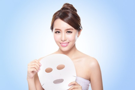 happy Young woman with cloth facial mask isolated on blue background, concept for skin care, asian 免版税图像
