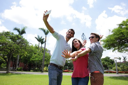 Group of happy friends taking a selfie on a blue sky in campus lawn, caucasian photo