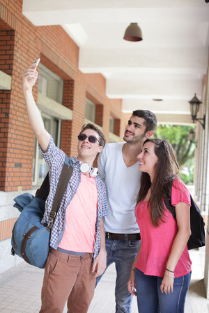 Group of happy friends taking a selfie by smart phone in campus , caucasian photo
