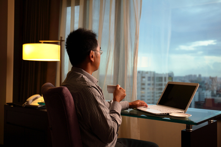 business man sit in a room and looking into the distance in hotel, concept of traveling business, dream, work at night etc  asian Imagens
