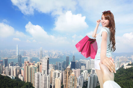 Happy Shopping in hong kong - beautiful young woman holding colored shopping bags with city background, asian photo