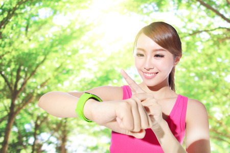 sport woman: Health sport woman wearing smart watch device with touchscreen doing exercises with green tree background, asian