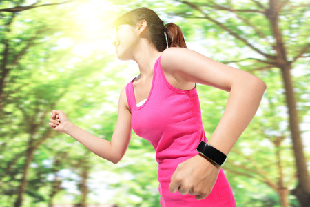 Health sport woman wearing smart watch device with touchscreen doing exercises with green tree background, asian photo