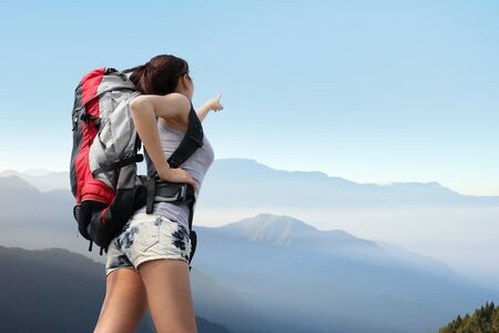 happy woman mountain hiker with backpack look view on the top of mountains. asian photo
