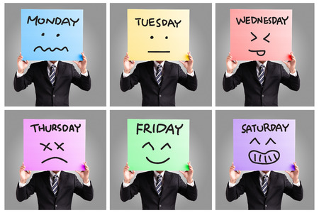face expression: Day of week and face expression - Young business man holding blank billboard card displaying face expression isolated on gray background