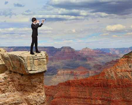 business man looks through a telescope on the top mountain. concept for business, leadership, success, photo
