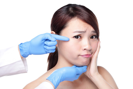 Plastic surgery touching the head of a beautiful female face, concept for micro plastic surgery, asian beauty Standard-Bild
