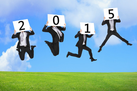 2015 new year business concept, Business man happy holding billboard and jumping or running on the green grass