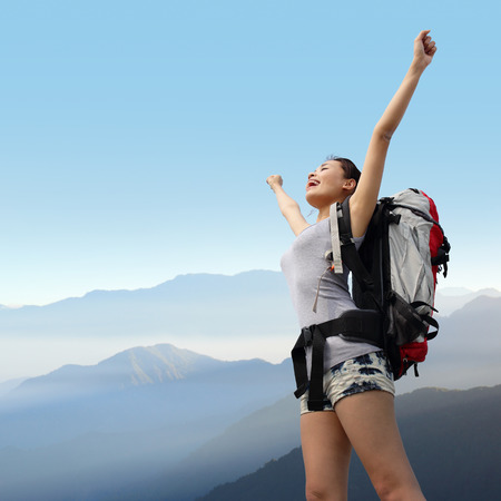 happy woman with backpack raised arm hands and looking to sky on the top of mountains. asian photo