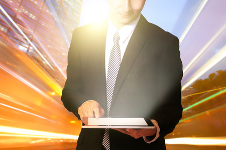 joy pad: business man using digital tablet with city traffic light trail at night, asia, china, hong kong