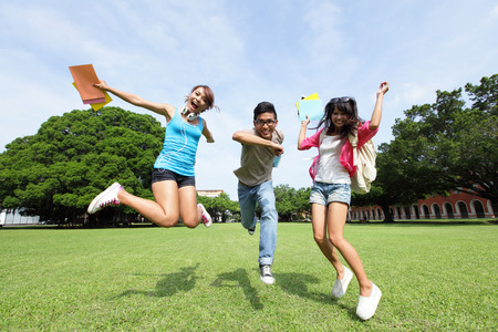 Happy College students jump and smile to you on campus lawn, asian photo