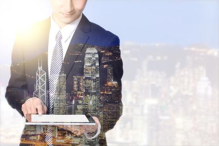 business asia: doppia esposizione e uomo d'affari della citt� - uomo d'affari con tavoletta digitale con la citt� di notte Orizzonte urbano, Asia, Cina, Hong Kong