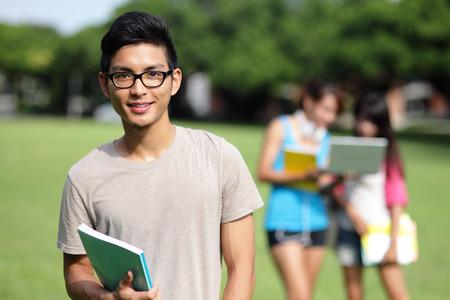 colegios: Estudiantes felices de la universidad sonr�en a usted en c�sped del campus, asi�tico