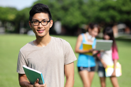 Happy College students smile to you on campus lawn, asian Stock Photo