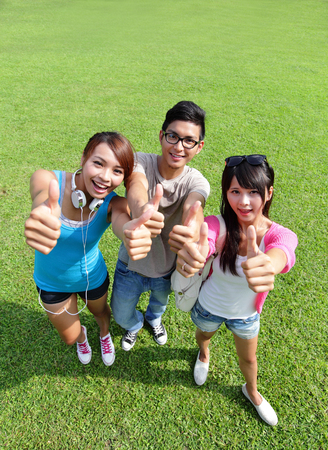 happy students in campus showing sign ok thumb, asian photo