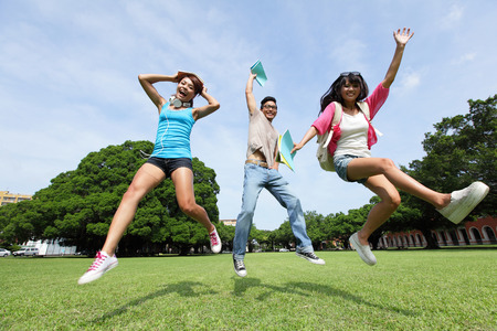 high park: Happy College students jump and smile to you on campus lawn, asian Stock Photo