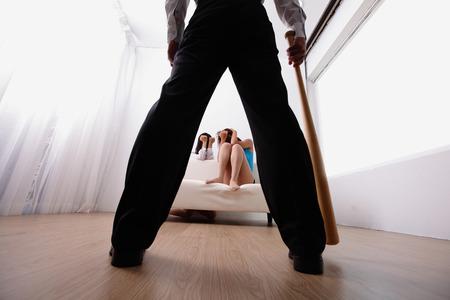 mujer hijos: violencia en el hogar - hombre que sostiene un bate de béisbol mira a su familia, asiático