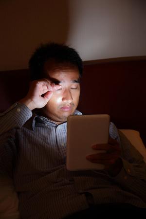 noche: Tablet PC va a doler los ojos en la oscuridad - tablet pc mirada hombre de negocios por la noche antes de dormir en la sala de estar, asiático