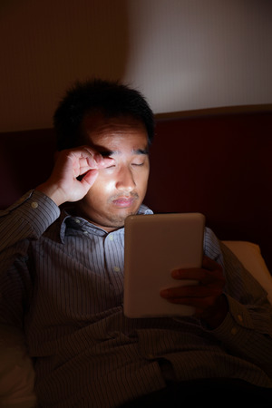 Tablet pc will hurt your eyes in the dark - business man look tablet pc late at night before sleep in the living room, asian photo
