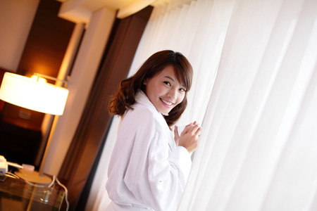 Young attractive woman smile holding a cup of coffee or tea in the morning, aisan