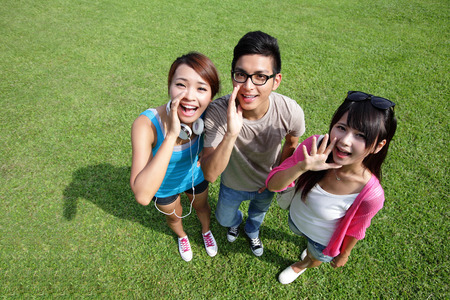 young happy university students shout and scream using her hands on campus lawn, asian Stock Photo