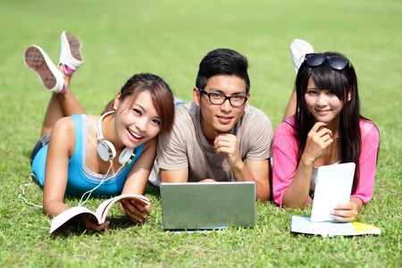 colegios: Estudiantes universitarios felices que usan la computadora port�til y tablet pc en c�sped del campus, asi�tico