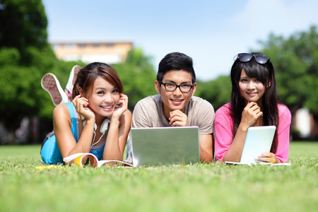 study group: Happy College students using laptop and tablet pc on campus lawn, asian