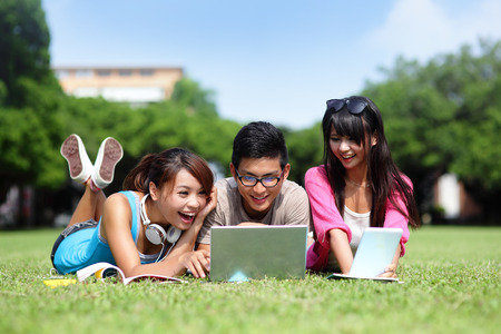 and in asia: Happy College students using laptop and tablet pc on campus lawn, asian