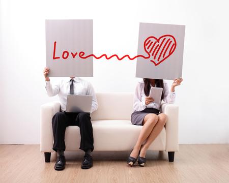 amor: Encontrar o amor ture na internet - homem e mulher usando o computador e tablet digital no sof
