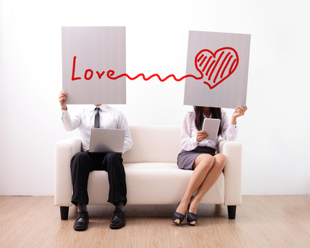 internet love: Find ture love on internet - man and woman using computer and digital tablet on sofa Stock Photo