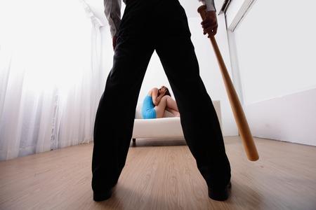 violencia intrafamiliar: violencia en el hogar - hombre que sostiene un bate de b�isbol mira a su familia, asi�tico