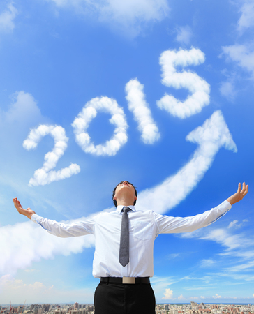 happy new year 2015, Business man hug 2015 (white arrow cloud and blue sky on sunny day) photo