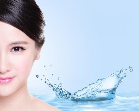 Beauty koncept Péče o pleť, krásná žena tvář s stříkající vodě izolovaných na modrém pozadí, asijské model