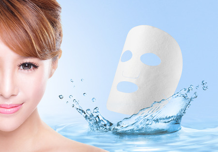 Beauty Skin care concept, Beautiful woman face with Water splashes and cloth facial mask isolated on blue background, asian model photo