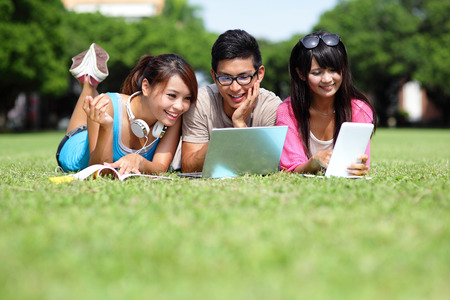 College Students: Happy College students using laptop and tablet pc on campus lawn, asian