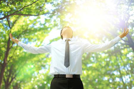 Tiefes Atmen sorglos Geschäftsmann mit Baum im Wald, asiatisch