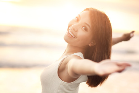 to raise: Smile Freedom and happiness woman on beach. She is enjoying serene ocean nature during travel holidays vacation outdoors. asian beauty Stock Photo